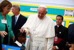 Pope Francis touches a student's head as he visits Our Lady Queen of Angels School in East Harlem in New York